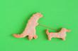 Leinwanddruck Bild - Homemade shortbread cookies on green background, top view. Dinosaur is walking with dog.