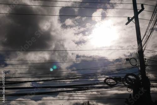Fototapeta Low Angle View Of Electricity Pylon With Tangled Cables Against Sky