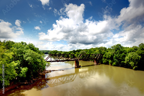 Fényképezés An old railroad trestle crossing the Catawba river in South Carolina with a beautiful sky