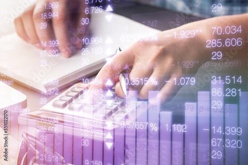 Cuadros en Lienzo Woman hand do analytics calculation on a calculator