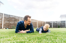 Father And Little Son Are Lying On The Green Lawn And Laugh. Dad And Toddler Play In The Backyard