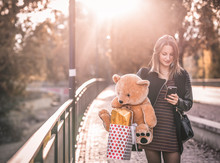 Girl Texts With Her Cell Phone And Holds Teddy Bear In Her Arms.