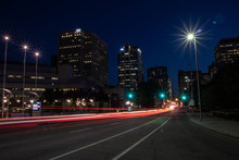 Light Trails On Road Amidst Bu...