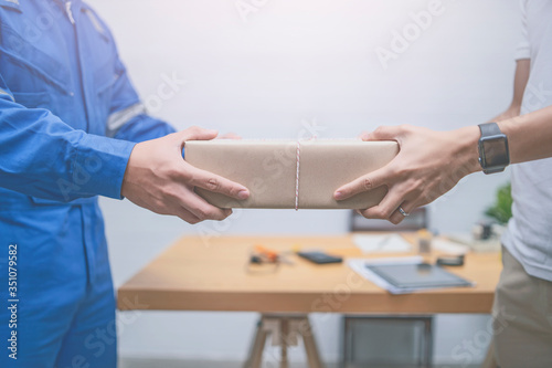 Delivery,mail and shipping,delivery man Checking Portable Device with Asian woman sign in digital Smartphone before receiving parcel or receive package,she appending signature in mobile phone at home Wallpaper Mural