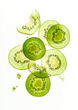 Backlit Kiwi Fruit Slices On White Background. Top View Layout