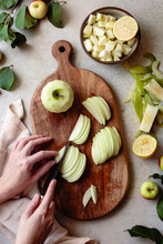 Hand Held Knife Slicing Apples On A Wooden Cutting Board.
