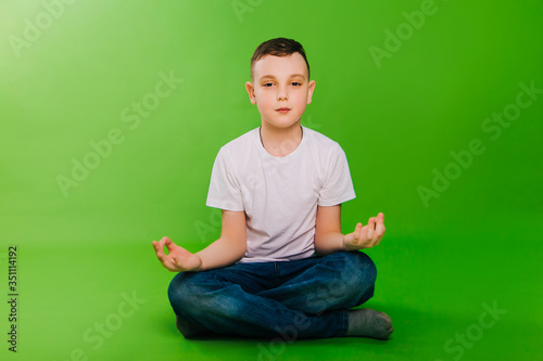Photo A boy in a white T-shirt on a green background did yoda