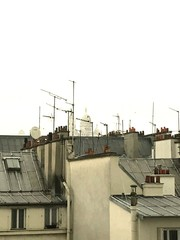Low Angle View Of Antennas On Roofs Against Clear Sky
