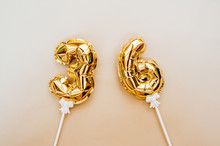 Small Foil Gold Balloons Numbers 36 Inflated With Helium On A White Stick On A Beige Delicate Background. Glittering Holiday Greeting Layout