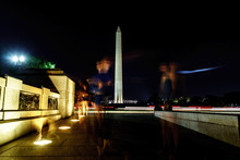 Blurred Motion Of People Walking On Footpath By Washington Monument Against Sky At Night