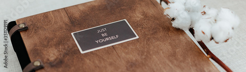 Luxury wooden photo book with just be yourself sign on linen natural background Wallpaper Mural