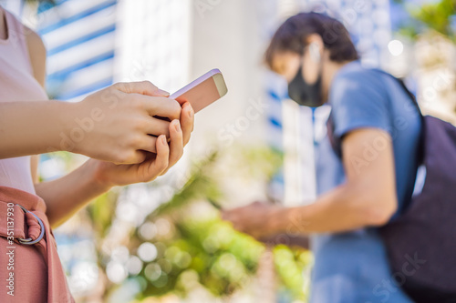 Obraz contact tracing app COVID-19 Pandemic Coronavirus Mobile Application - people Wearing Face Mask Using Smart Phone App in City Street to Aid Contact Tracing in Response to the 2019-20 Coronavirus - fototapety do salonu