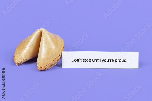 Photo Whole fortune cookie with motivational text 'Don't stop till you're proud' on pu