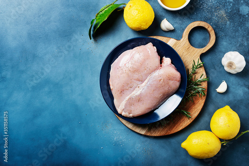 Fototapeta chicken breast with lemons, rosemary and pepper obraz