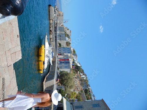 Fotografia Rear View Of Woman Standing On Paving Stone By Sea Against Sky