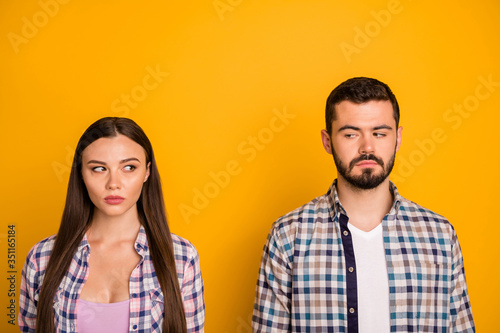 Obraz Closeup photo pretty lady handsome guy couple stand keep distance not smiling look eyes suspicious responsible people citizens wear casual plaid shirts isolated yellow color background - fototapety do salonu