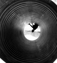 Upside Down Image Of Boy Sitting In Pipe