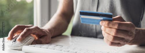 Man hand holding credit card and using laptop at home, Businessman or entreprene Fototapeta