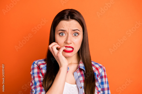 Obraz Close-up portrait of her she nice attractive nervous worried straight-haired girl wearing checked shirt having panic attack biting nails isolated on bright vivid shine vibrant orange color background - fototapety do salonu
