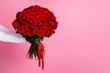 Photo of cropped man arms hold big one hundred red bright roses bunch giving secret admirer delivery service worker valentine day romance concept isolated pink color background