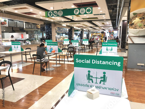 Obraz BANGKOK, THAILAND- June 21, 2020: Social distancing for COVID-19 disease pandemic prevention in Tesco Lotus food court dining table public area for new normal keeping people distance - fototapety do salonu
