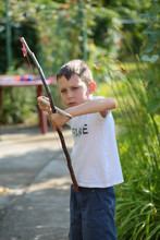 Chłopiec Bawi Się  W Ogrodzie łukiem Samodzielnie Zrobionym Z  Drewnianego Patyka