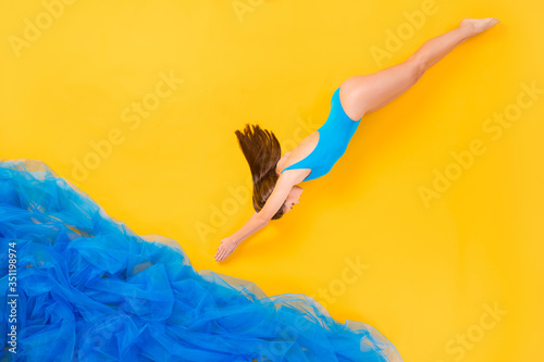 Obraz Top view above high angle flat lay flatlay lie concept full length body size view of attractive thin girl swimming diving deep water isolated on bright vivid shine vibrant yellow color background - fototapety do salonu