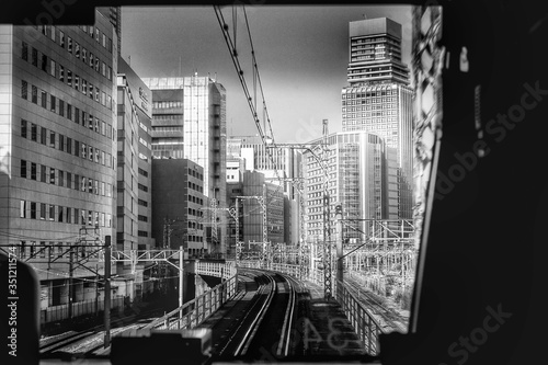 Railroad Tracks Amidst Buildings In City Seen From Train Windshield