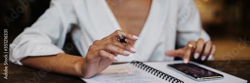Vászonkép Woman writing down on her notebook