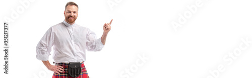 smiling Scottish redhead bearded man in red tartan kilt pointing with finger isolated on white, website header