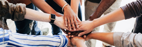 Fototapeta Group of diverse people stacking hands in the middle