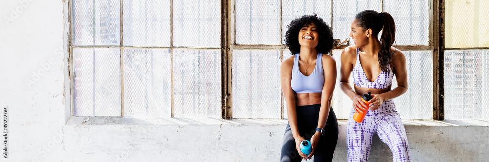 Fototapeta Sportive women talking in a gym while drinking water - obraz na płótnie