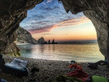 Hiking Equipment In Cave By Sea Against Sky During Sunset