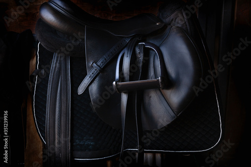 Fototapeta Shiny black leather horse saddle in the dark stable , with stirrup, ready for riding  obraz