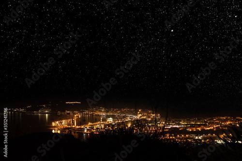 Ceuta city illuminated at night under the stars