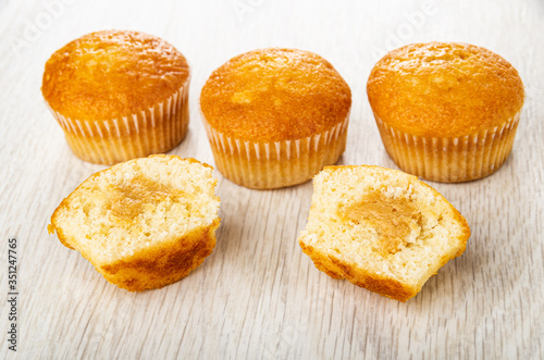 Fototapeta Muffins, halves of muffin with cream on table