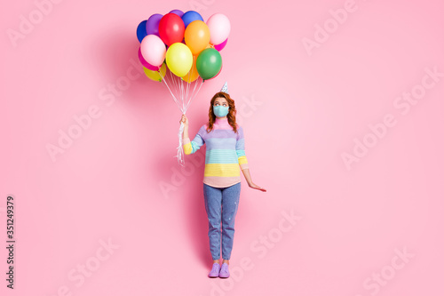 Obraz Full length photo of pretty lady quarantine arrange birthday party best friend hold many air balloons unexpected surprise wear face mask sweater jeans shoes isolated pink color background - fototapety do salonu