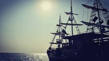 Silhouette Ship Sailing On Sea Against Clear Sky