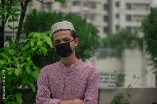 Cuadros en Lienzo Muslim boy with traditional punjabi wears protective mask and celebrating ramada