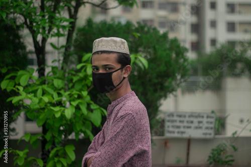 Fotografía Muslim boy with traditional punjabi wears protective mask and celebrating ramada