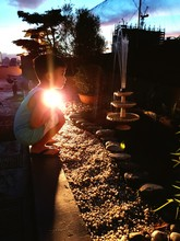 Full Length Side View Of Cute Boy Crouching While Looking At Fountain During Sunset