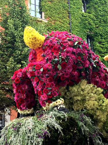 Obraz na plátně Sculpture Made From Flowers Against Ivies Growing On Building