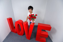 Young Asian Boy Holding A Bouquet Of Roses