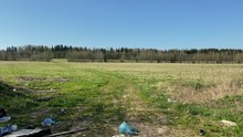 The Road Into A Green Spring Field Is Blocked By An Illegal Dump Of Old Things. Plastic Bags, Bottles, Dishes, Toys, Tires, Pieces Of Wood Are Lying. Clear Day With Blue Sky