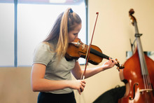 Teenage Girl Playing Violin In Classroom