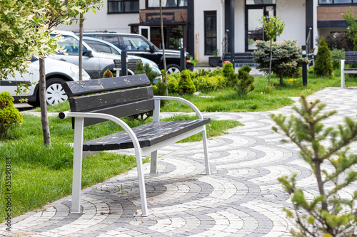 Fotografía Wooden and metal bench in a beautiful green courtyard with many plants in a gated community