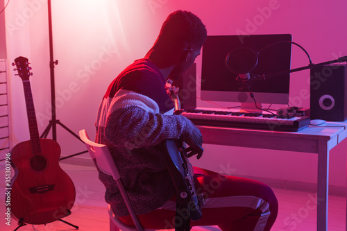Photo Create music and a recording studio concept - African american man guitarist rec
