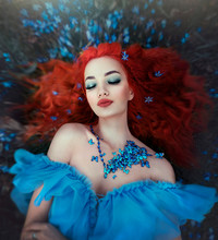 Butterfly Girl In A Necklace Of Blue Butterflies Lies In The Forest In Flowers. Female Fairy In A Fairy Forest. Art.