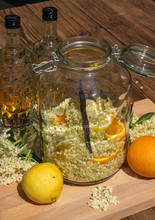 In The Large Preserving Jar On The Cutting Board Are The Fresh Elderflowers, Oranges And Lemon Slices And The Vanilla Pod In The Background Are The Vodka Bottles For The Elderflower Liqueur