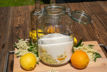 In The Large Preserving Jar On The Cutting Board Are The Fresh Elderflowers, Oranges And Lemon Slices, Sugar And The Vanilla Pod In The Background Are The Vodka Bottles For The Elderflower Liqueur